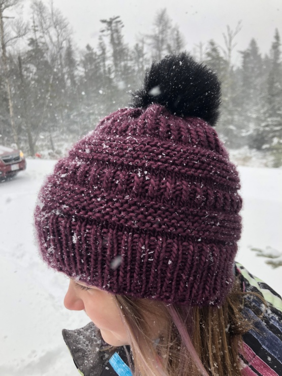 girl in knit purple hat with black pompom in snow storm