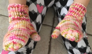 white, pink, and green mittens